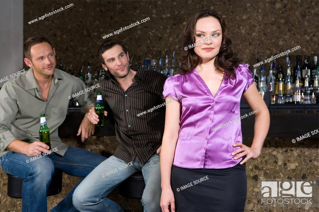 Stock Photo: Men looking at a woman in bar.