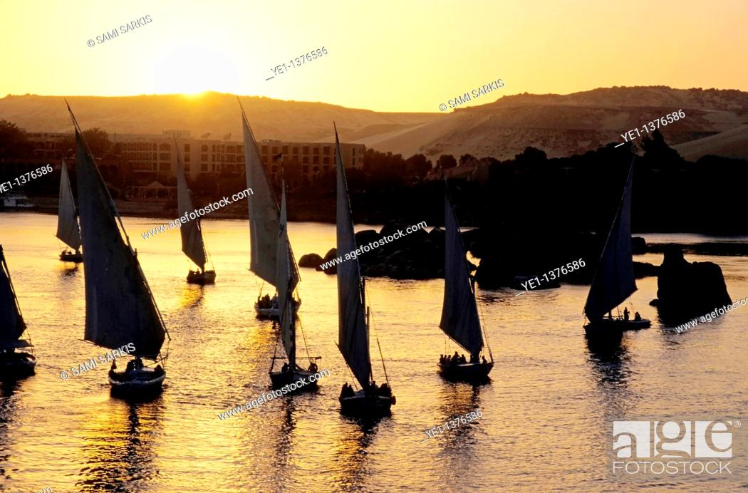 Stock Photo: Feluccas sailing on the Nile river at sunset, Aswan, Egypt.