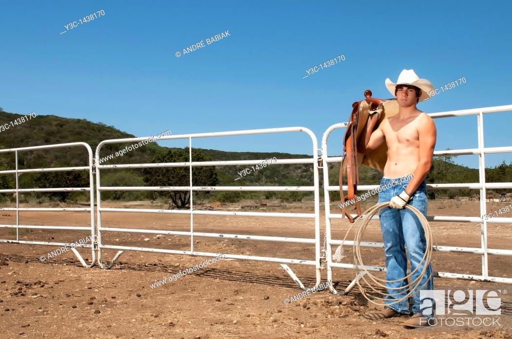 Stock Photo: Sexy cowboy with saddle on a ranch.