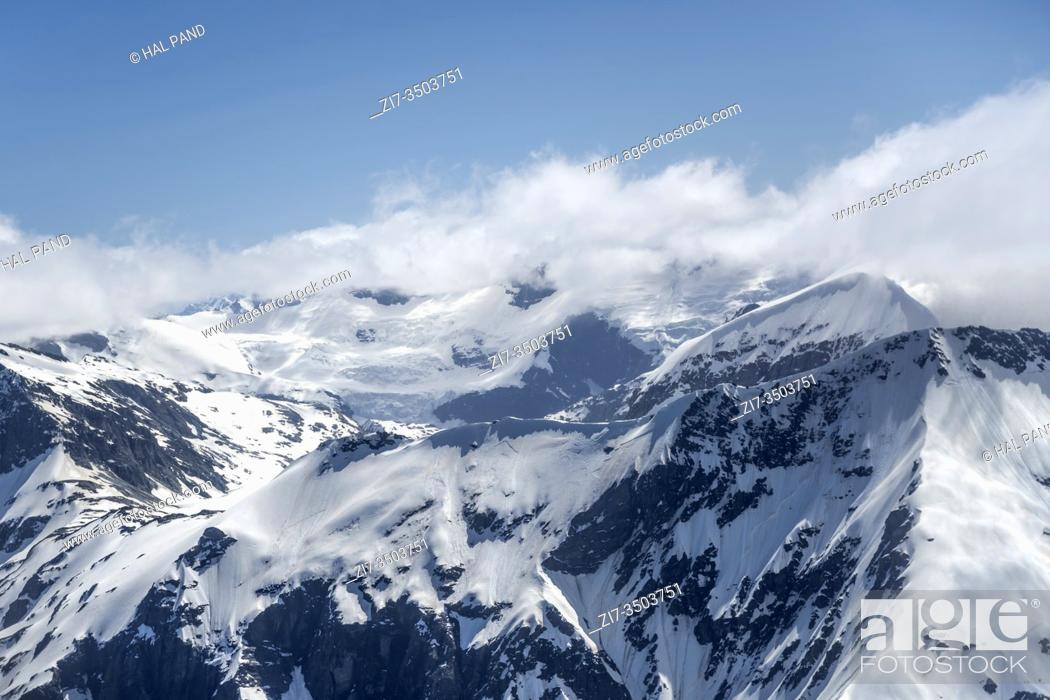 Stock Photo: aerial, from a glider, of cliffs of Fastness Peak with Mt. Aspiring range among clouds in background, shot in bright spring light from east, West Coast.