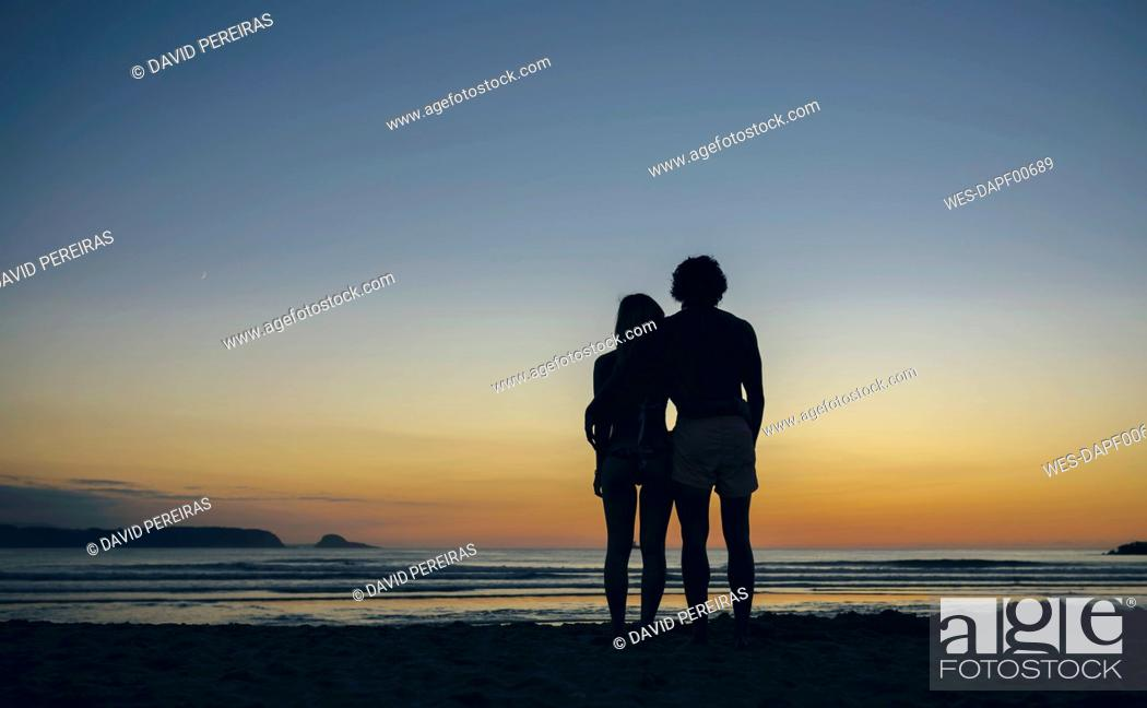 Stock Photo: Young couple watching the sunset on the beach.