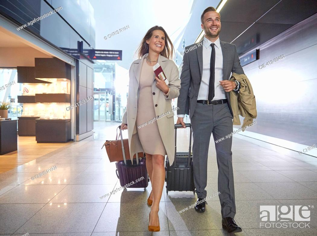 Stock Photo: Business people walking pulling suitcases in airport concourse.