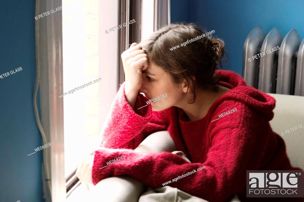 Stock Photo: Young woman sitting next to a window.