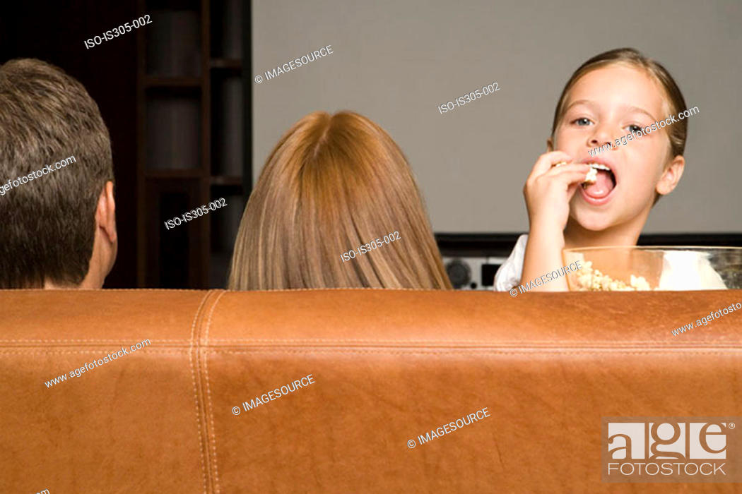 Stock Photo: Girl eating popcorn with family.