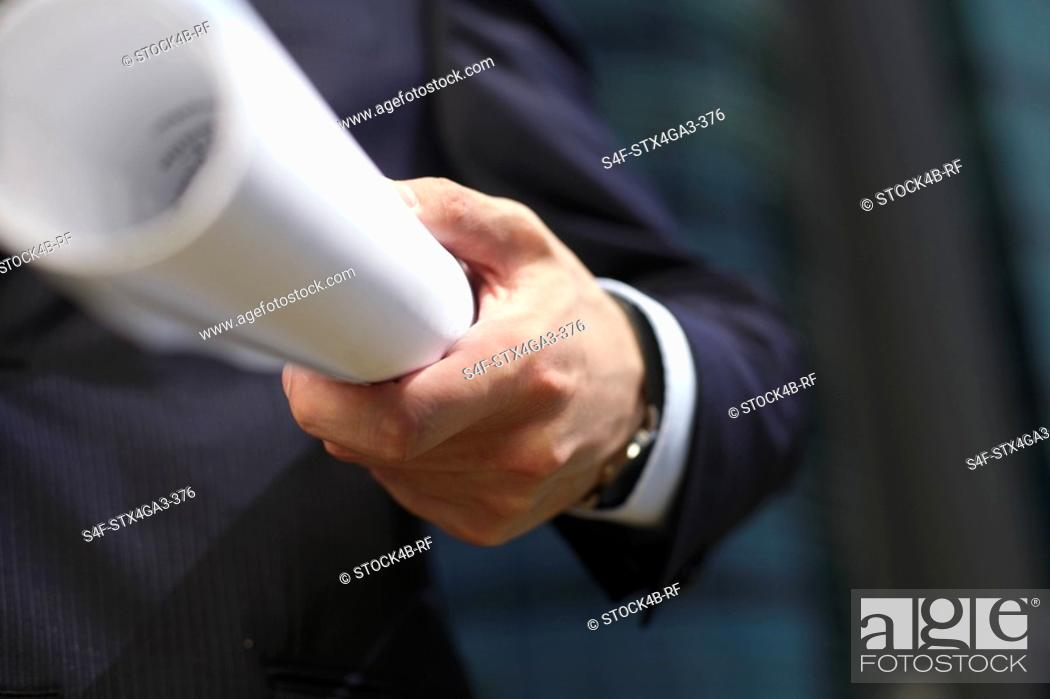 Stock Photo: Hand holding a paper roll.