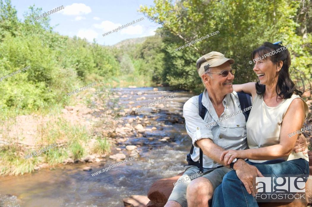 Stock Photo: Multi-ethnic senior couple hugging next to stream.