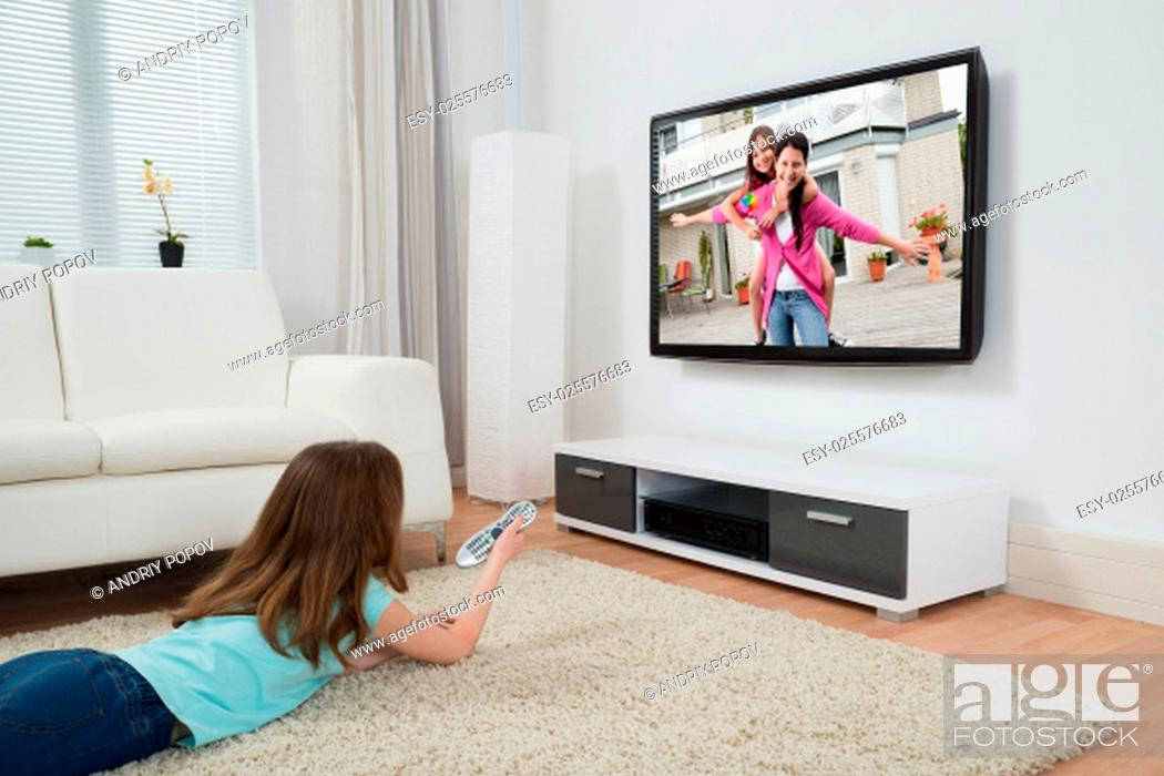 Stock Photo: Girl With Remote Control Watching Movie On Television In Living Room.