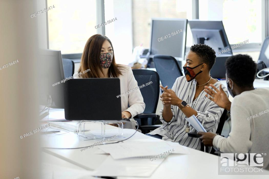 Stock Photo: Business people in face masks talking in office meeting.