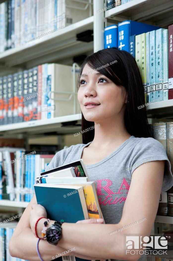 Imagen: Young woman studying in the library and looking away with smile.