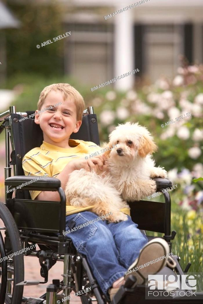 Stock Photo: Young boy in wheelchair smiling and holding dog.