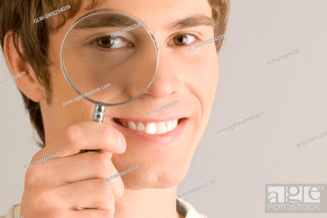 Stock Photo: Close-up of a young man looking through a magnifying glass.
