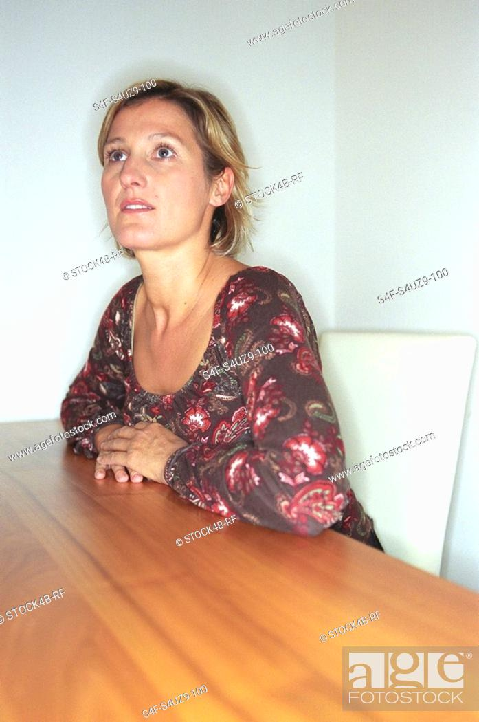Stock Photo: Blonde Woman sitting at a Table.