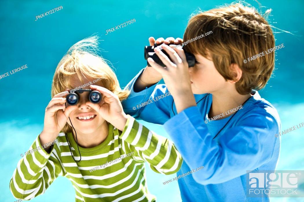 Stock Photo: Two boys looking through binoculars.