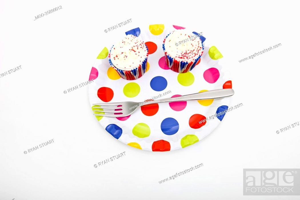 Stock Photo: High angle view of cupcakes in multicolored plate against white background.