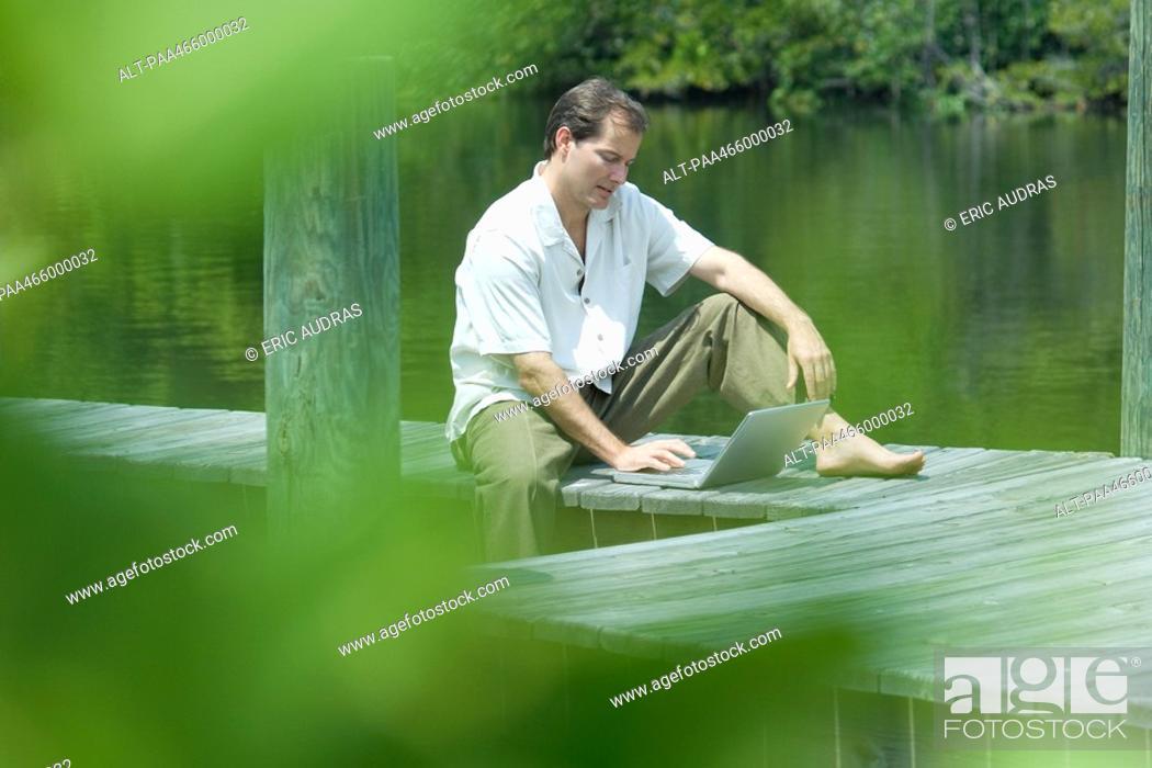 Stock Photo: Man sitting on dock using laptop computer, view through foliage.