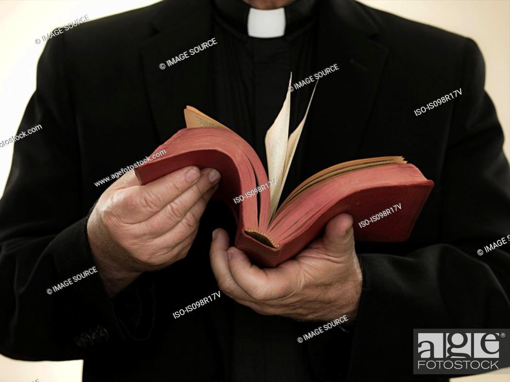 Stock Photo: Priest holding a bible.
