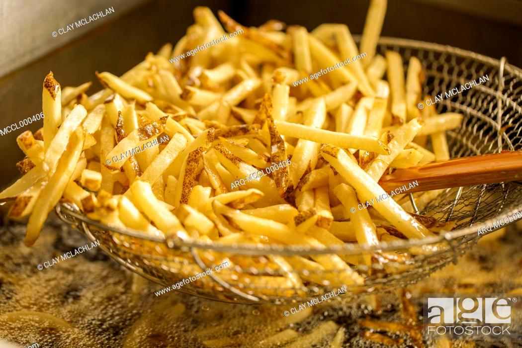 Stock Photo: Stack Of Fries In A Fryer Basket.