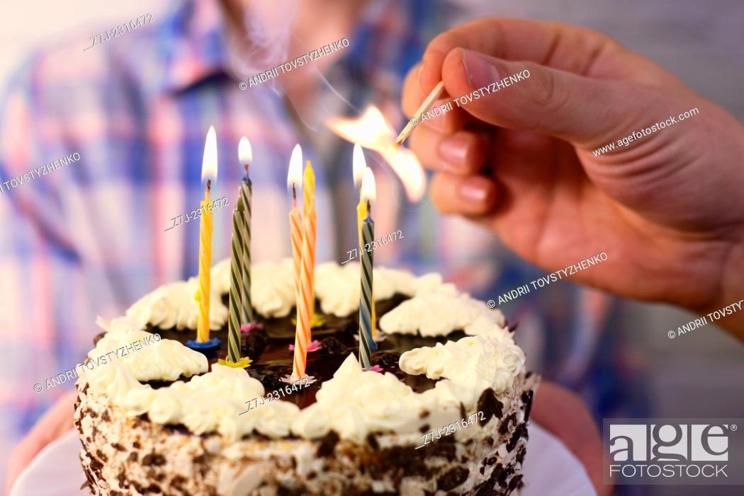 Stock Photo: male hand lights the candles on the birthday cake.
