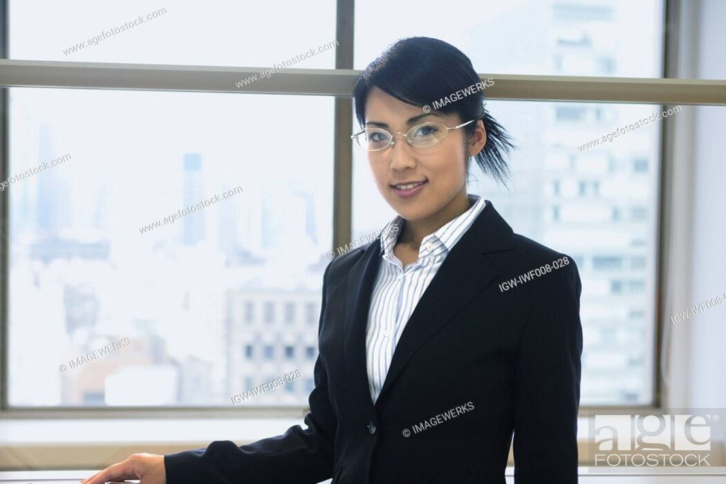 Stock Photo: A woman standing beside the window as she smiles at the camera.