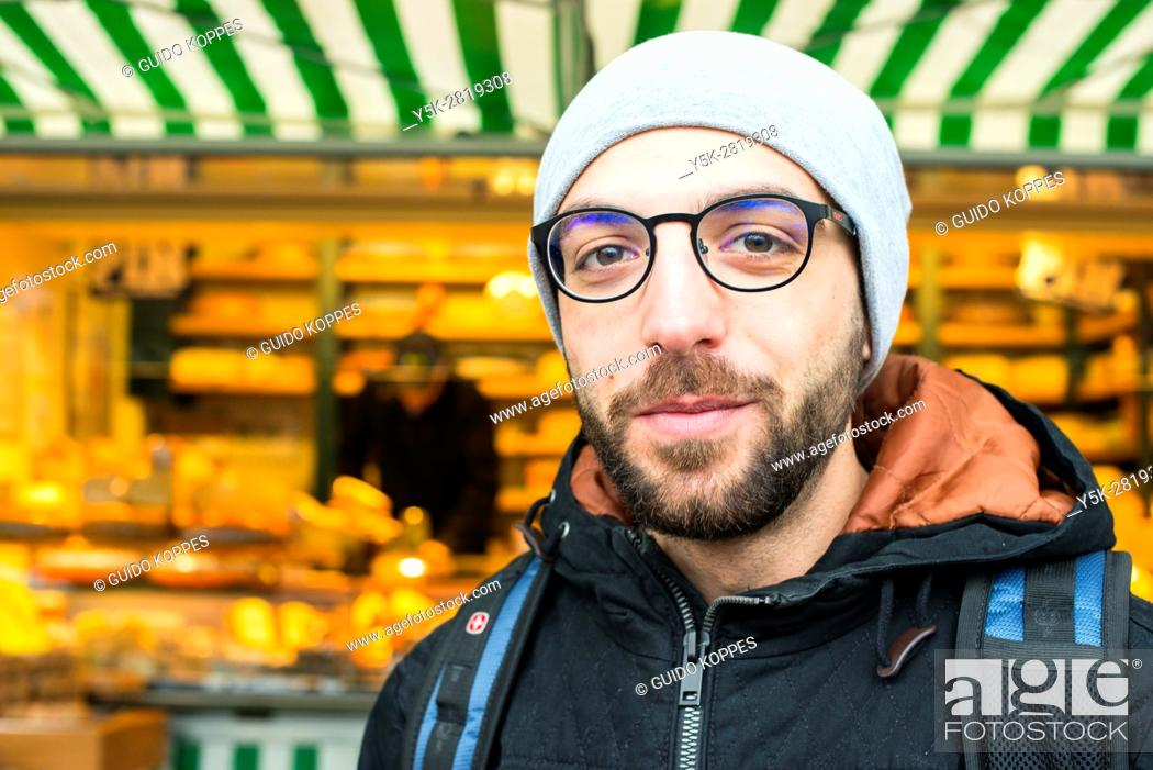 Stock Photo: Tilburg, Netherlands. Former Syrian refugee visiting a Dutch market cheese stall at the weekly saturday market as part of his integration process.