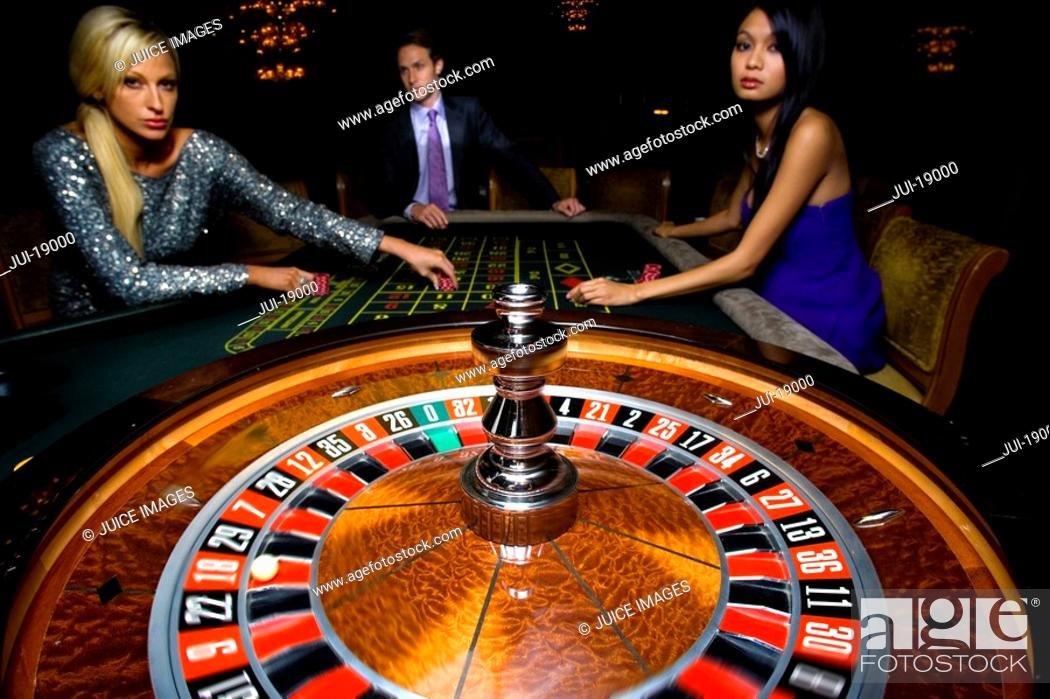 Stock Photo: Man flanked by women, gambling at roulette table, portrait.
