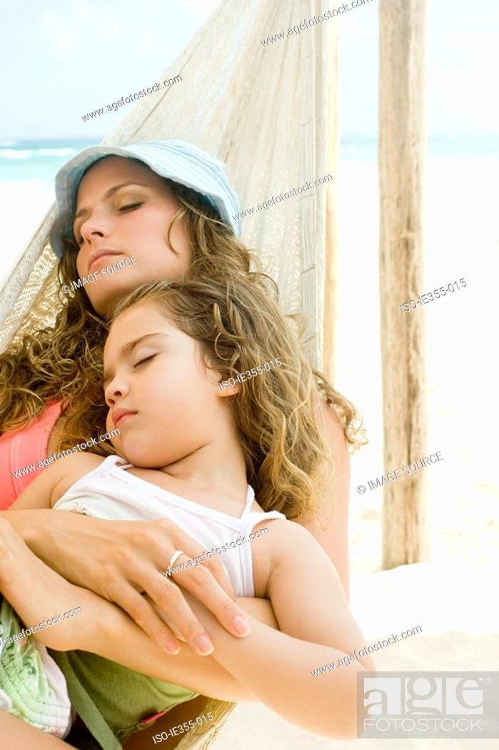 Stock Photo: A mother and daughter sleeping on a hammock.