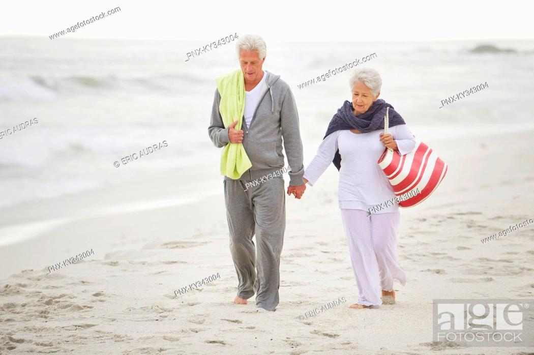 Stock Photo: Senior couple walking on the beach.