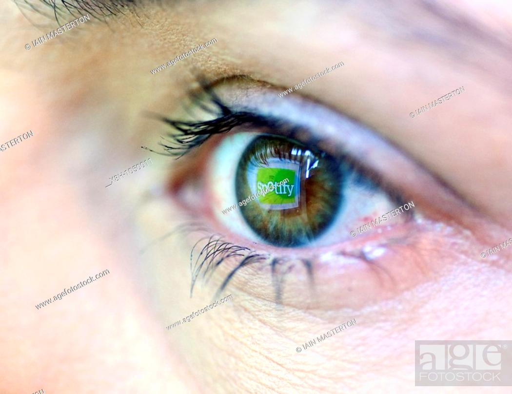 Stock Photo: Logo from digital music website Spotify reflected from computer screen in woman`s eye.