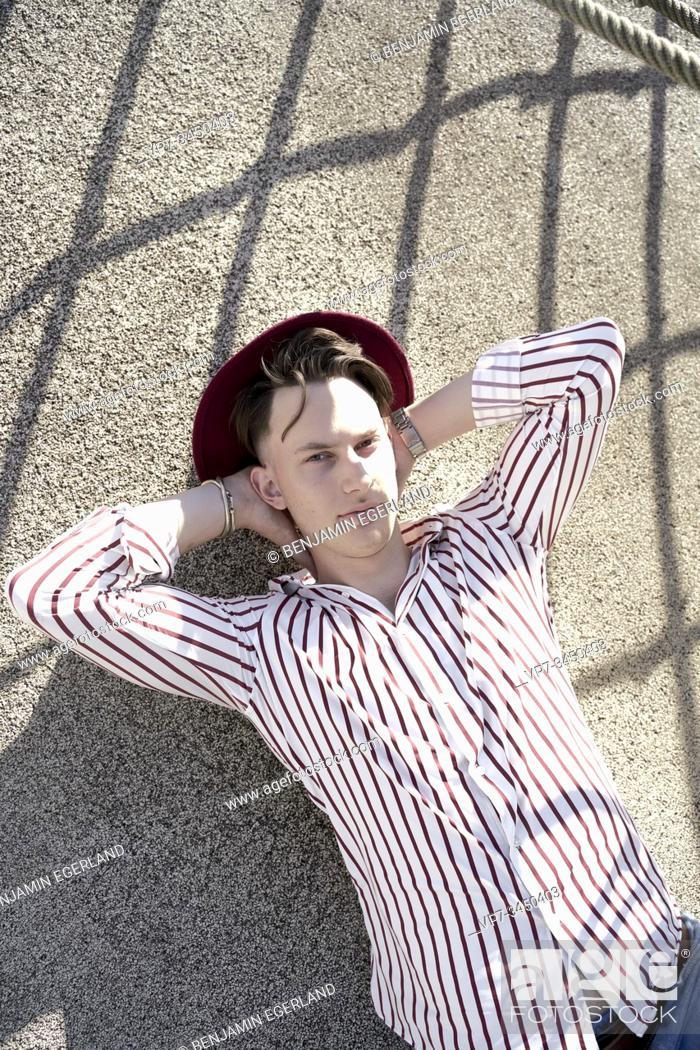 Imagen: Man wearing hat, lying on the floor. Munich, Germany.