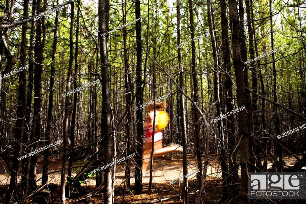 Stock Photo: Woman jogging through a thick forest.