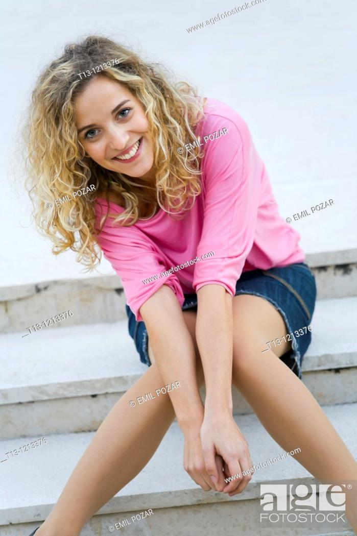 Stock Photo: Very happy young woman is sitting on steps.