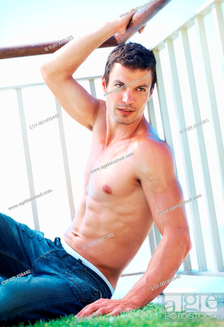 Stock Photo: Handsome shirtless muscular man posing next to railings.