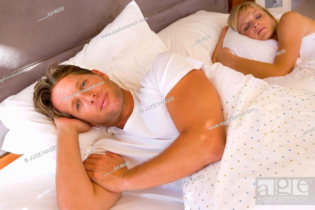 Stock Photo: Young couple lying in bed beneath covers, smiling, portrait, elevated view.