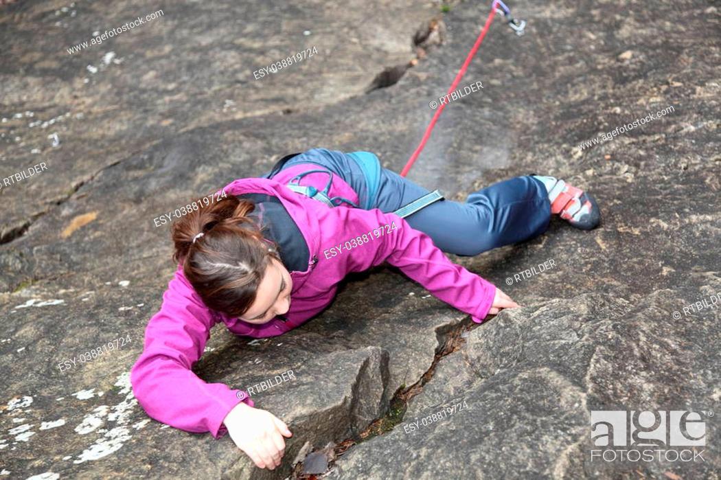 Stock Photo: a girl is free climbing a rock.