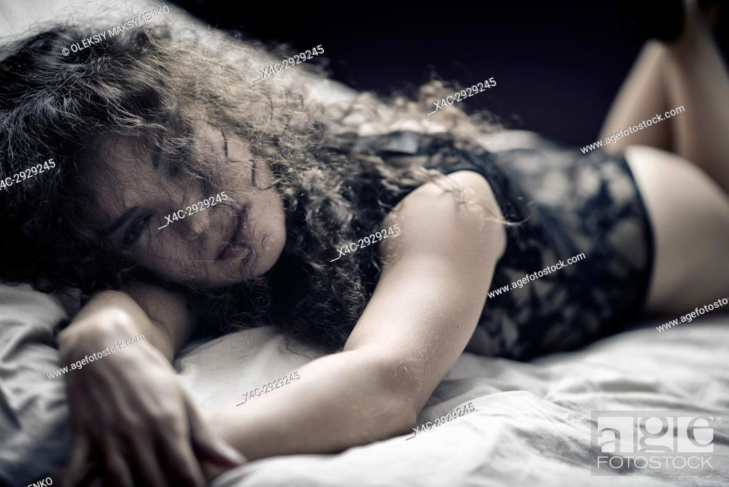 Stock Photo: Sensual expressive candid portrait of a young beautiful woman lying on a bed in underwear with her face partially covered by long curly hair.