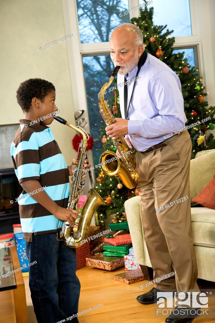 Imagen: African American grandfather playing saxophone with grandson.