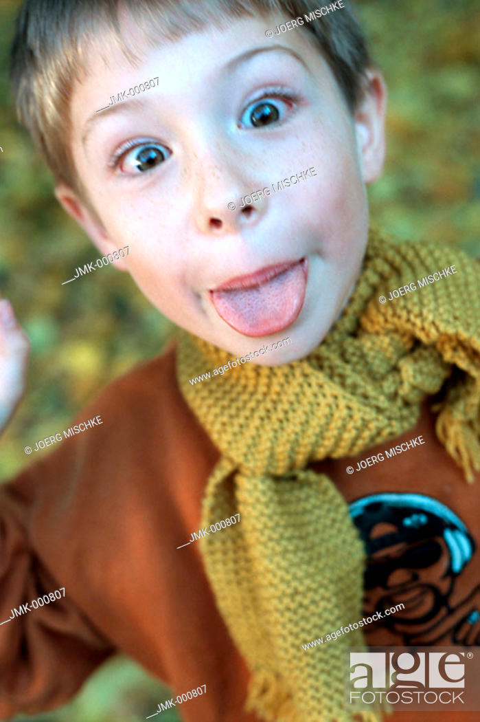 Stock Photo: Little boy in the autumnal wood, forest, sticking out his tongue.