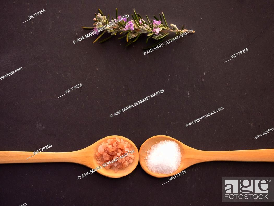 Imagen: Wooden spoons with marine common salt and pink himalayan salt and a rosemary twig on a slate plate.