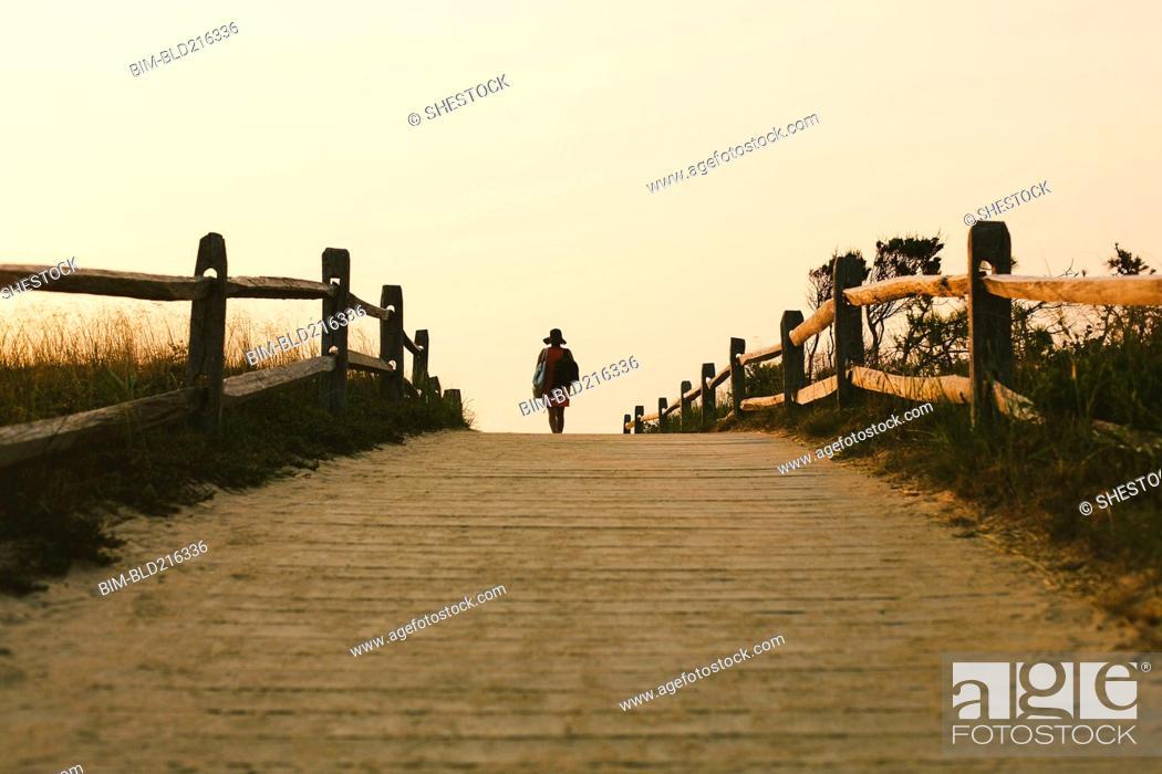 Stock Photo: Silhouette of woman walking on wooden walkway.