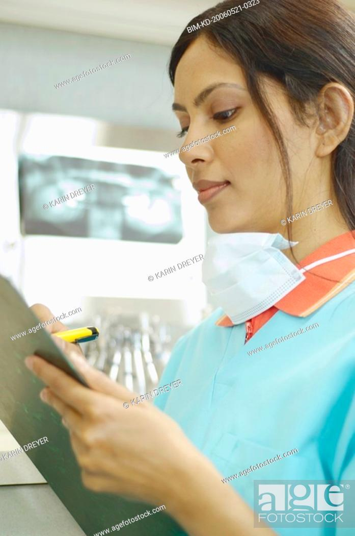 Stock Photo: Indian female dental assistant writing on chart.
