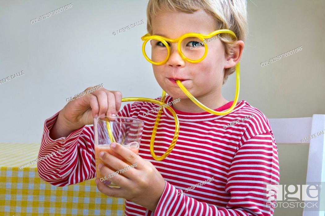 Stock Photo: Boy drinking through curly straw.