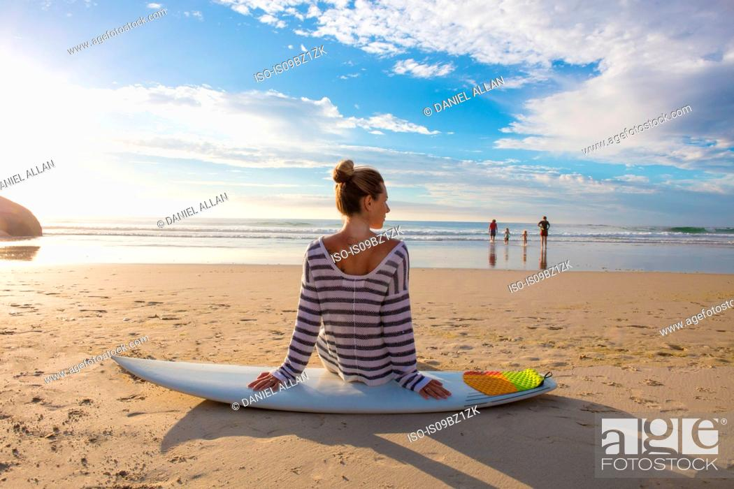 Stock Photo: Female surfer sitting on surfboard at beach, rear view, Cape Town, Western Cape, South Africa.