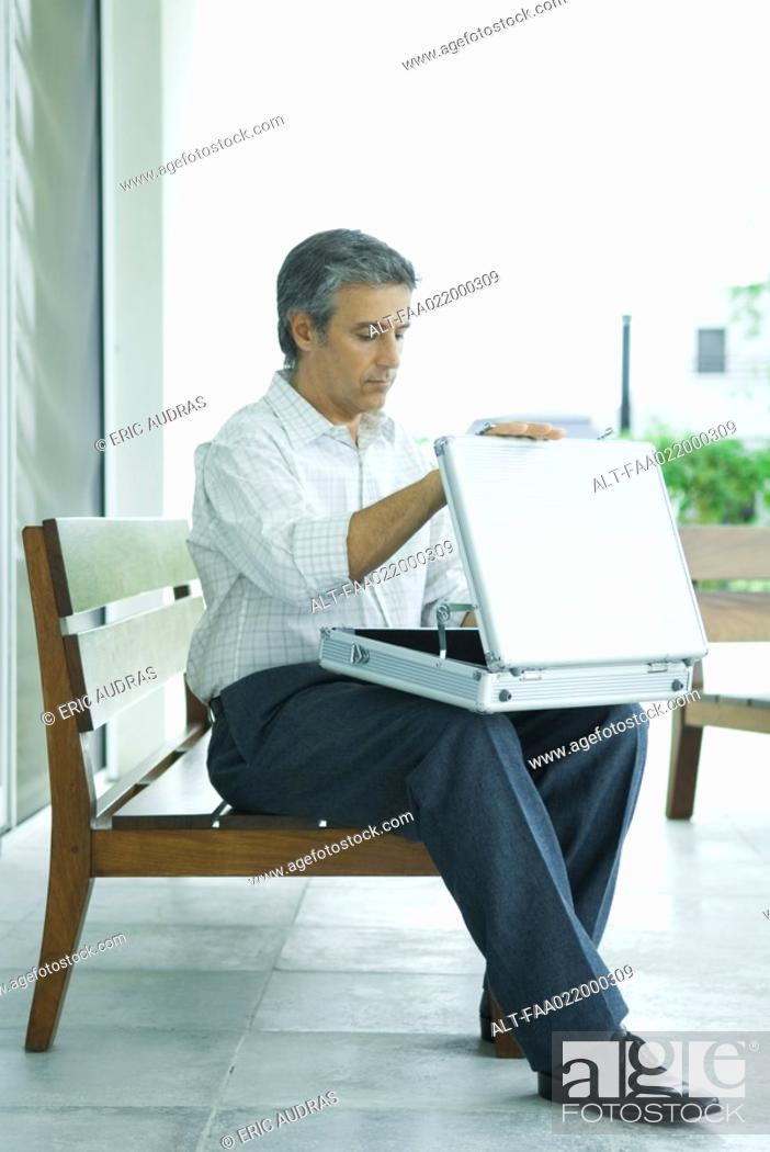 Stock Photo: Mature man sitting on bench, opening briefcase, full length.