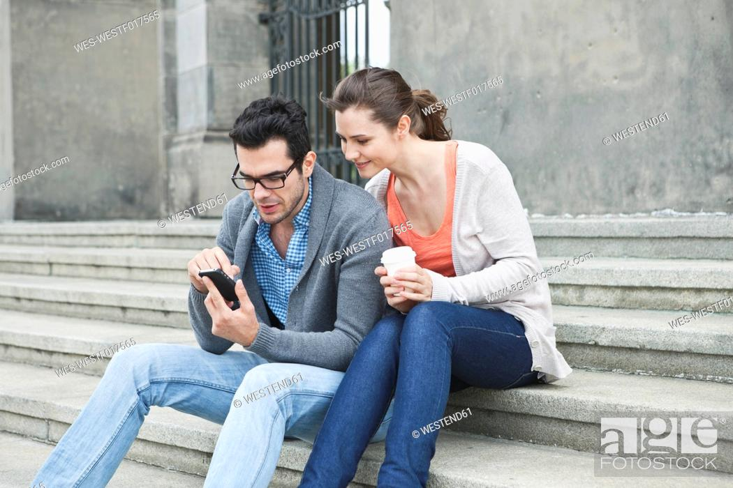 Stock Photo: Germany, Berlin, Couple using cell phone on stairway.
