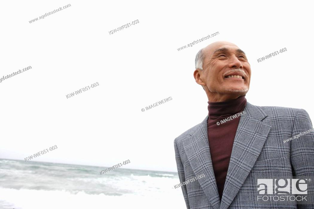 Stock Photo: Senior man at beach, smiling.