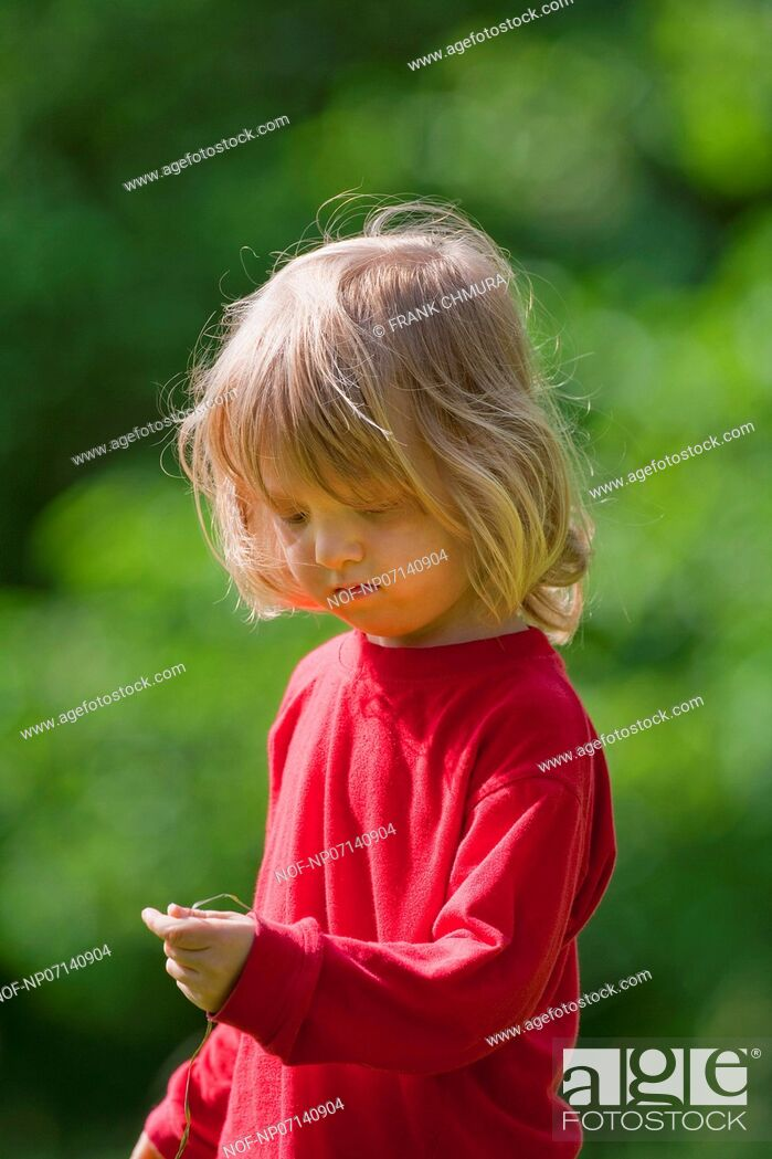 Stock Photo: boy with long blond hair and grass straw in the garden.