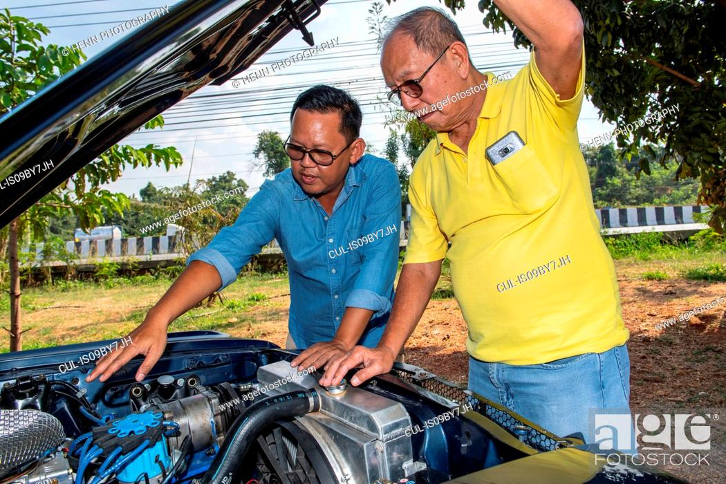 Imagen: Friends inspecting engine of classic American muscle car.
