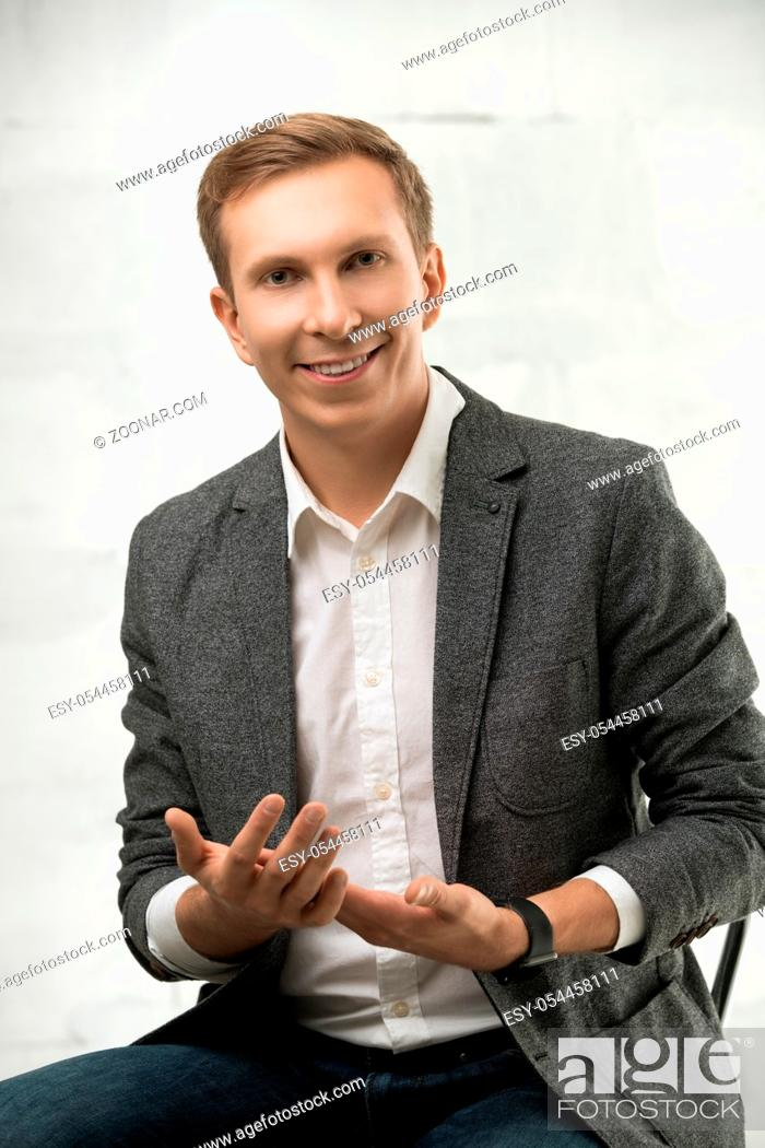 Stock Photo: Young fair handsome male wearing white shirt, jacket and jeans sitting on a chair with a gentle smile portrait against white wall.
