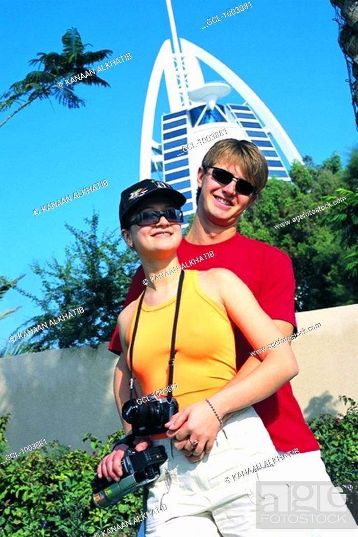 Stock Photo: Western tourist couple in front of Burj Al Arab hotel in Dubai, UAE.