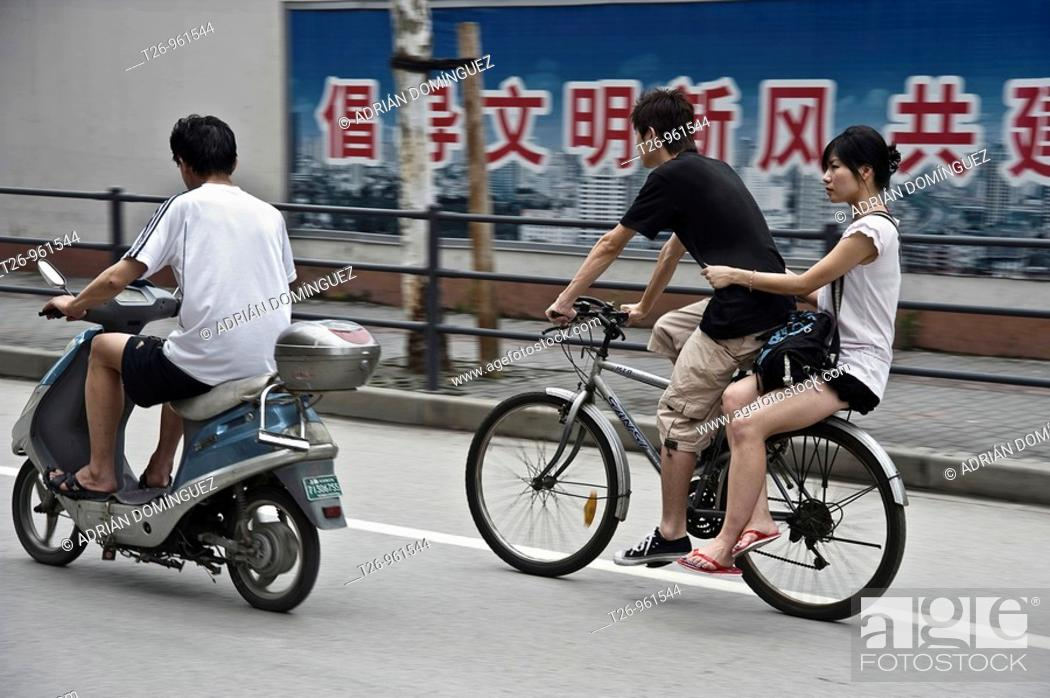 Stock Photo: A man carries a woman on a bike in the street. Shanghai, China.